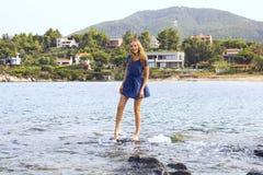 Giovane donna che sta sulla pietra nel mare e nella risata Fotografia Stock