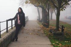 Giovane donna che sta sulla via il giorno nebbioso di autunno Fotografia Stock Libera da Diritti