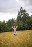 Giovane donna che sta in un campo di autunno con alta erba Fotografie Stock Libere da Diritti