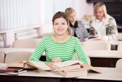 Giovane donna che studia allo scrittorio con i lotti dei libri Fotografia Stock