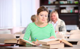 Giovane donna che studia allo scrittorio con i lotti dei libri Fotografie Stock Libere da Diritti