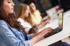 Giovane donna che studia con il computer portatile sullo scrittorio bianco Fotografia Stock