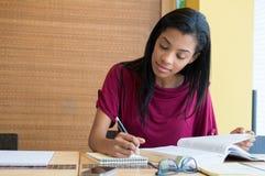 Giovane donna che studia nella biblioteca Immagine Stock