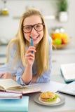 Giovane donna che studia nella cucina Fotografie Stock