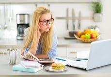 Giovane donna che studia nella cucina Fotografie Stock Libere da Diritti