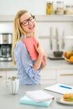 Giovane donna che studia nella cucina Fotografia Stock