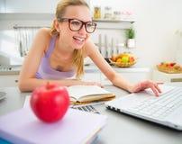 Giovane donna che studia nella cucina Immagine Stock Libera da Diritti