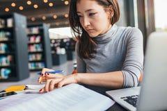 Giovane donna che studia su un libro e che prende le note Immagine Stock Libera da Diritti