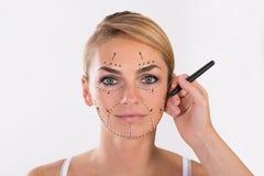 Giovane donna che subisce la chirurgia di ringiovanimento del viso immagini stock libere da diritti