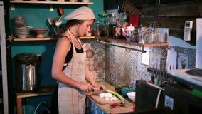 Giovane donna che taglia cipolla a pezzi sul tagliere di legno stock footage