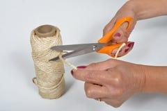 Giovane donna che taglia un pezzo di corda fotografia stock libera da diritti