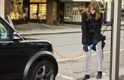 Giovane donna che tappa in un'automobile elettrica Fotografie Stock
