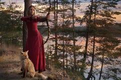 Giovane donna che tende con l'arco e la freccia fotografia stock libera da diritti