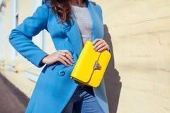 Giovane donna che tiene borsa alla moda e che porta cappotto blu d'avanguardia Vestiti ed accessori femminili della primavera Mod fotografia stock