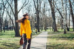 Giovane donna che tiene borsa alla moda e che porta maglione giallo Vestiti ed accessori femminili della primavera Modo immagini stock