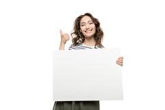 Giovane donna che tiene carta bianca in bianco e che mostra pollice su fotografia stock libera da diritti