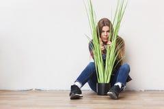 Giovane donna che tiene grande pianta verde che si siede contro la parete Immagine Stock
