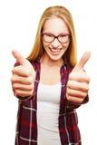 Giovane donna che tiene i suoi pollici su Fotografia Stock