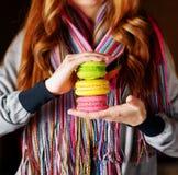 Giovane donna che tiene il macaron della pasticceria francese in caffè immagine stock libera da diritti