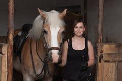 Giovane donna che tiene il suo cavallo in stalla Fotografie Stock