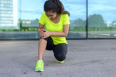 Giovane donna che tiene il suo ginocchio doloroso Fotografia Stock