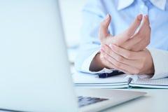 Giovane donna che tiene il suo primo piano del polso Dolore dal per mezzo del computer Dolore della mano di sindrome dell'ufficio immagine stock