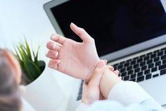 Giovane donna che tiene il suo primo piano del polso Dolore dal per mezzo del computer Dolore della mano di sindrome dell'ufficio fotografia stock libera da diritti