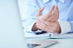 Giovane donna che tiene il suo primo piano del polso Dolore dal per mezzo del computer Dolore della mano di sindrome dell'ufficio fotografie stock libere da diritti