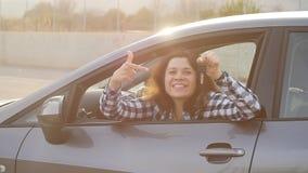 Giovane donna che tiene la chiave ad una nuova automobile stock footage