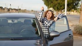 Giovane donna che tiene la chiave ad una nuova automobile archivi video