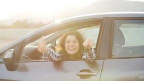 Giovane donna che tiene la chiave ad una nuova automobile video d archivio