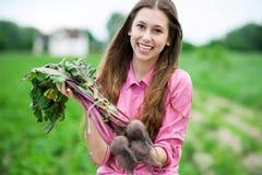 Giovane donna che tiene le barbabietole fresche Immagine Stock