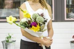 Giovane donna che tiene mazzo asimmetrico moderno dei fiori fotografia stock