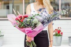 Giovane donna che tiene mazzo asimmetrico moderno dei fiori alla via fotografie stock libere da diritti