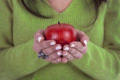Giovane donna che tiene mela rossa sana nelle mani fotografia stock