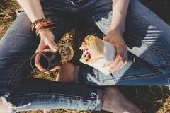 Giovane donna che tiene panino e vetro freschi di vino rosso, vista superiore Immagine Stock