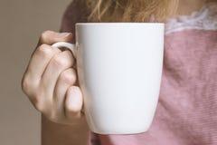 Giovane donna che tiene tazza bianca Immagini Stock