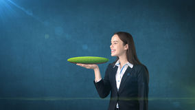 Giovane donna che tiene terra 3D sulla palma aperta della mano con copyspace vuoto, fondo isolato dello studio Concetto di affari Fotografie Stock