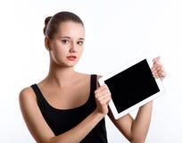 Giovane donna che tiene un computer della compressa sopra fondo bianco Immagine Stock