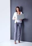 Giovane donna che tiene un computer portatile, stante sul fondo grigio Fotografia Stock Libera da Diritti