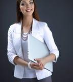 Giovane donna che tiene un computer portatile, stante sul fondo grigio Fotografie Stock