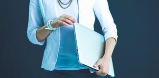 Giovane donna che tiene un computer portatile, stante sul fondo grigio Fotografie Stock Libere da Diritti