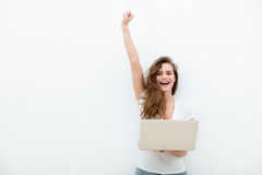 Giovane donna che tiene un computer portatile su bianco Immagine Stock