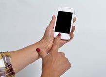 Giovane donna che tiene un telefono cellulare immagine stock libera da diritti