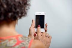 Giovane donna che tiene un telefono cellulare immagini stock
