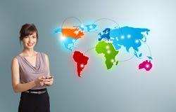 Giovane donna che tiene un telefono e che presenta la mappa di mondo variopinta Fotografia Stock