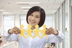 Giovane donna che tiene una catena delle figure Cutted di carta Immagini Stock
