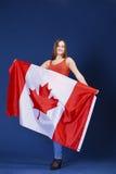 Giovane donna che tiene una grande bandiera canadese Fotografie Stock Libere da Diritti