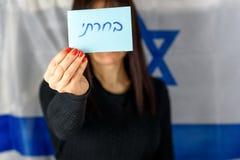 Giovane donna che tiene voto Front Of Face sul fondo israeliano della bandiera Testo che ebraico ho votato su scheda di votazione fotografie stock