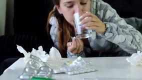 Giovane donna che tossisce e che prende una pillola stock footage